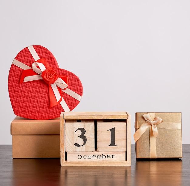 Hölzerner retro- kalender von den blöcken, vom weihnachtsdekorativen baum und von den pappschachteln