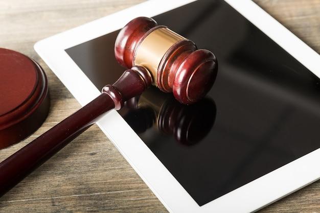Hölzerner richterhammer auf digitalem tablet. justiz- und rechtskonzept