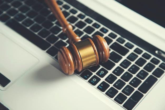 Hölzerner richterhammer auf tastatur-laptop-computer