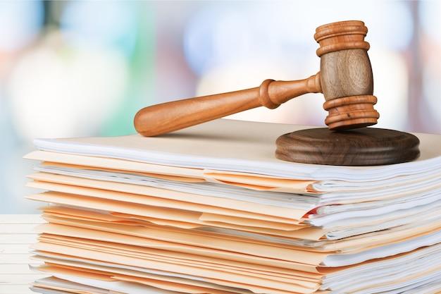 Hölzerner richterhammer mit exemplar über dem hintergrund. justiz- und rechtskonzept