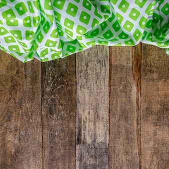 Hölzerner rustikaler hintergrund mit grüner serviette.