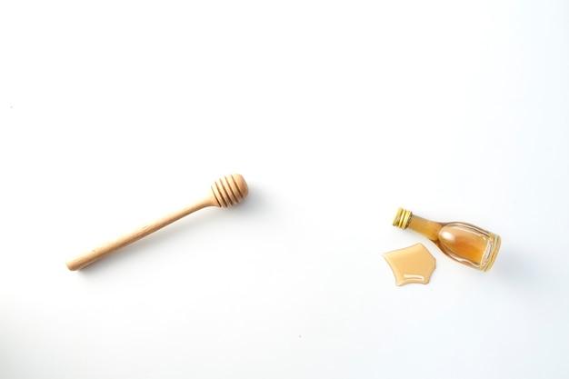 Hölzerner schöpflöffel des honigs und wenig honigflasche auf weiß