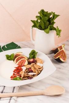 Hölzerner schöpflöffel nahe gesundem frühstück mit tadellosen blättern im krug auf marmorzähler
