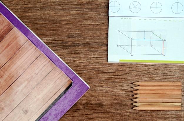 Hölzerner schreibtisch der schule mit papierbuch, bleistiften und mathematikbuch schulbank