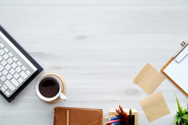 Hölzerner schreibtisch des arbeitsplatzbüros mit computertastatur, blatt und tasse kaffee. draufsicht mit kopienraum