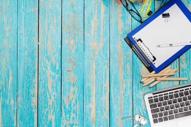 Hölzerner schreibtisch mit laptop und bürozubehör. ansicht von oben
