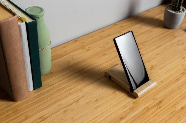 Hölzerner schreibtisch mit schwarzem smartphone und büchern