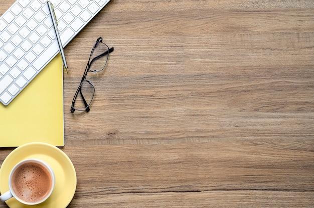 Hölzerner schreibtisch mit tasse kaffee, weißer tastatur und versorgungsmaterialhintergrund