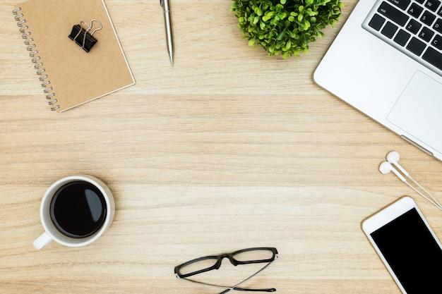 Hölzerner schreibtischtisch mit laptop, kaffee und versorgungen.
