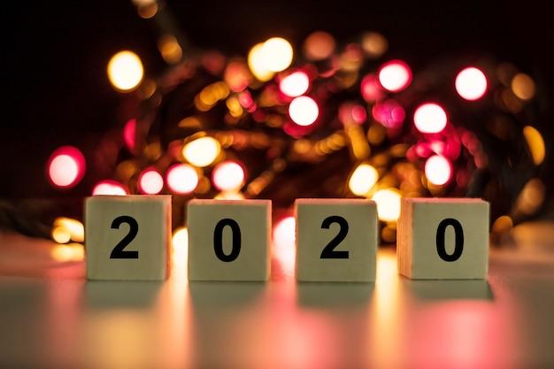 Hölzerner stock des neuen jahres 2020 auf rotem bokeh