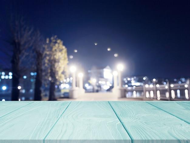 Hölzerner strukturierter schreibtisch vor stadtlicht nachts