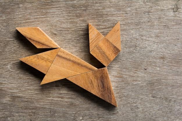 Hölzerner tangram als laufende katzenform auf altem hölzernem hintergrund