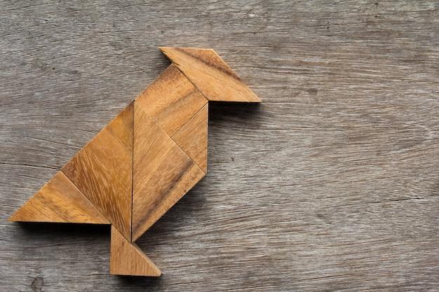 Hölzerner tangram als vogelform auf altem hölzernem hintergrund