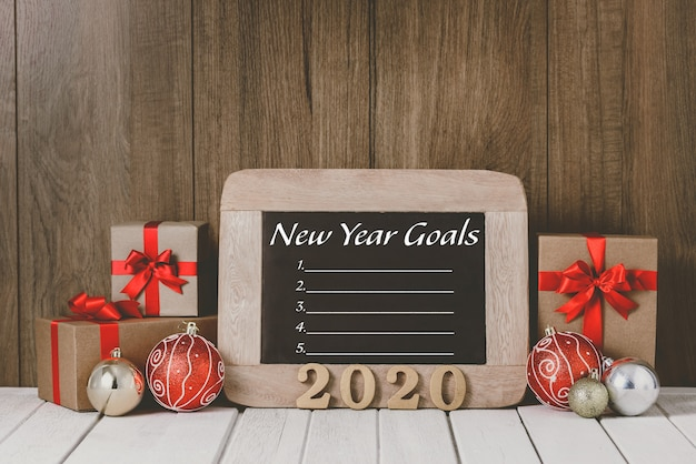 Hölzerner text 2020 und weihnachtsverzierungen und die ziel-liste des neuen jahres geschrieben auf tafel über hölzernem