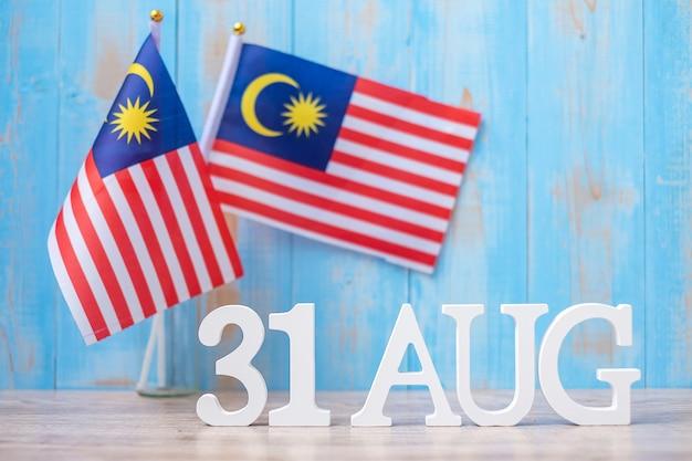 Hölzerner text vom 31. august mit malaysia-flaggen. unabhängigkeitstag von malaysia