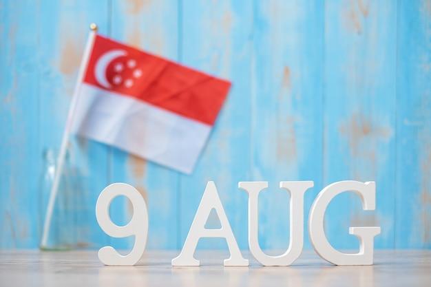 Hölzerner text vom 9. august mit miniaturflaggen von singapur. singapur-unabhängigkeitstag, stadtstaat-nationalfeiertag und fröhliche feierrepublik-konzepte