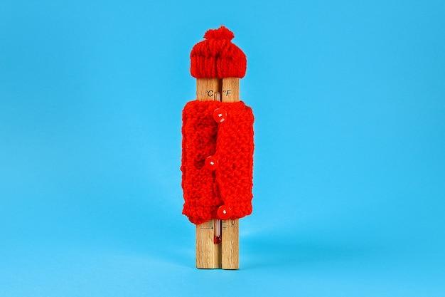 Hölzerner thermometer, einen roten hut und eine strickjacke auf einem blau tragend