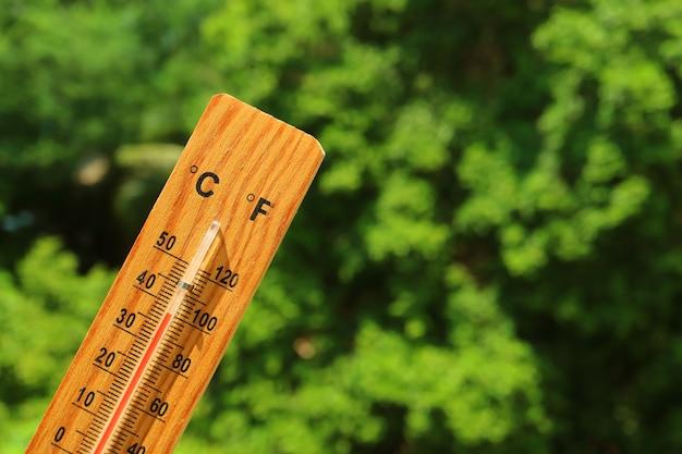 Hölzerner thermometer im sommersonnenlicht, das hohe temperatur zeigt