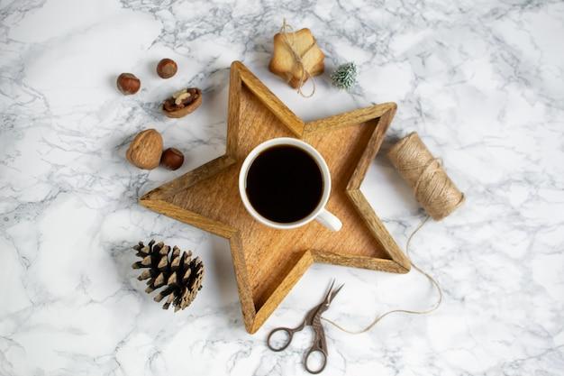 Hölzerner tray star cup mit schwarzem kaffee-weihnachtsmorgen-geschenkbox-laptop-neujahrs-konzept