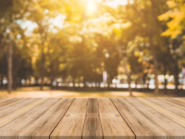 Hölzerner vorstand leerer tisch vor verschwommenem hintergrund. perspektive braune holztisch über unschärfe bäume im wald hintergrund - kann verwendet werden mock up für display oder montage ihrer produkte. herbstsaison.