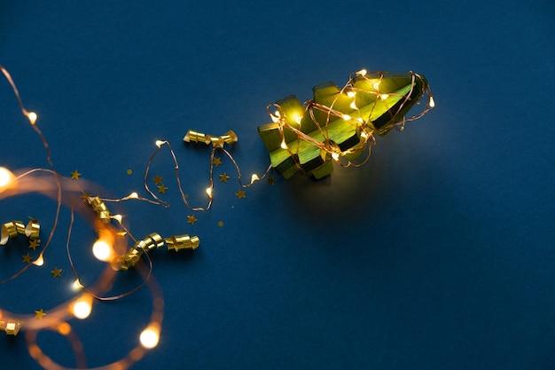 Hölzerner weihnachtsbaum in form einer rakete auf einem dunkelblauen hintergrund. jet trail der girlande. das konzept von weihnachten. bild der rakete