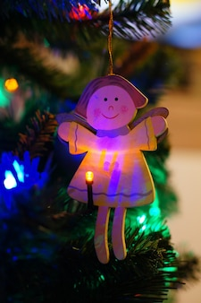 Hölzerner weihnachtsbaumengelschmuck, der an einem baum mit einem beleuchteten weihnachtslicht hängt