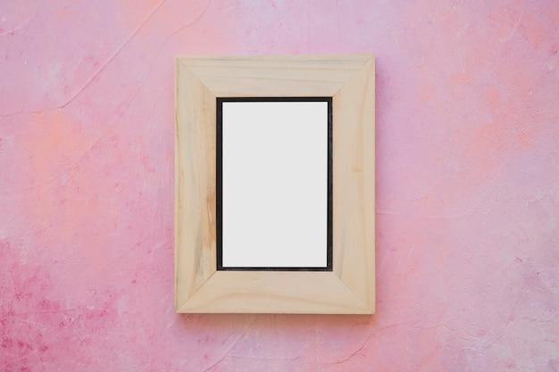 Hölzerner weißer bilderrahmen auf gemalter rosafarbener wand
