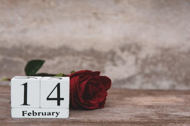 Hölzerner weißer blockkalender und rotrose