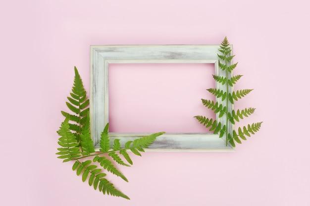 Hölzerner weißer fotorahmen und grünblätter auf leichtem rosa