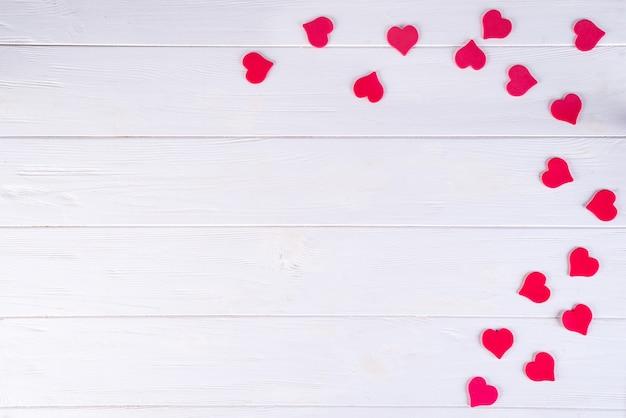 Hölzerner weißer hintergrund mit dekorativem rotem herzen valentinstag.