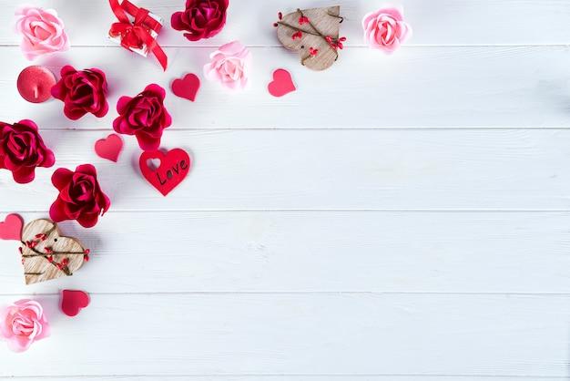 Hölzerner weißer hintergrund mit roten herzen und blumen. valentinstag