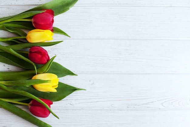 Hölzerner weißer hintergrund mit tulpen. konzeptionsfeiertag, 8. märz