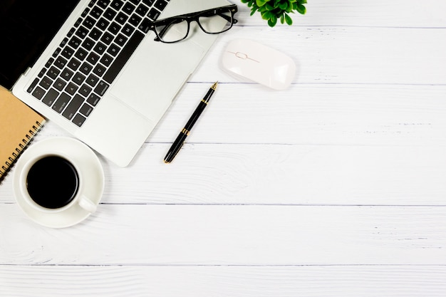 Hölzerner weißer schreibtisch mit leerem notizbuch und anderem büroartikel