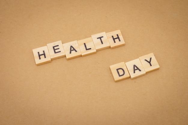 Hölzerner wort gesundheitstag unter verwendung universaltagkonzept des hintergrundes und gesundheitstag als hintergrund