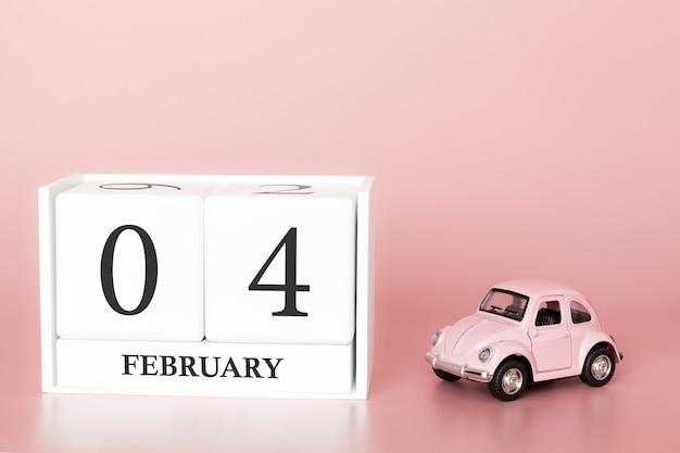 Hölzerner würfel der nahaufnahme 4. februar. tag 4 des februar-monats, kalender auf einem rosa mit retro- auto.