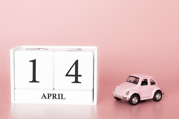 Hölzerner würfel der nahaufnahme am 14. april. tag 14 des aprilmonats, kalender auf einem rosa mit retro- auto.