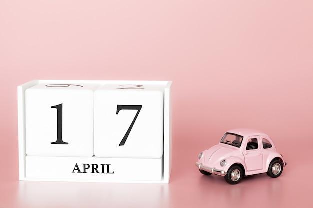 Hölzerner würfel der nahaufnahme am 17. april. tag 17 des aprilmonats, kalender auf einem rosa mit retro- auto.