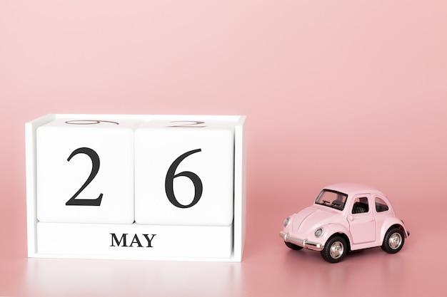 Hölzerner würfel der nahaufnahme am 26. mai. tag 26 des monats mai, kalender auf einem rosa hintergrund mit retro-auto.