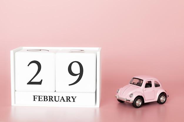 Hölzerner würfel der nahaufnahme am 29. februar. tag 29 des februar-monats, kalender auf einem rosa mit retro- auto.