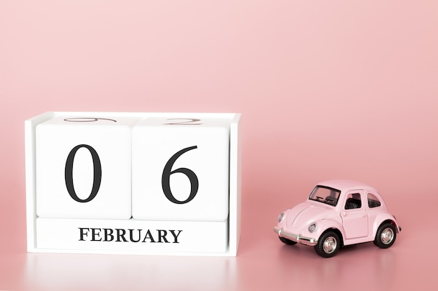 Hölzerner würfel der nahaufnahme am 6. februar. tag 6 des februar-monats, kalender auf einem rosa mit retro- auto.
