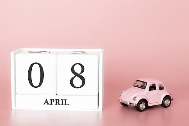 Hölzerner würfel der nahaufnahme am 8. april. tag 8 des aprilmonats, kalender auf einem rosa mit retro- auto.