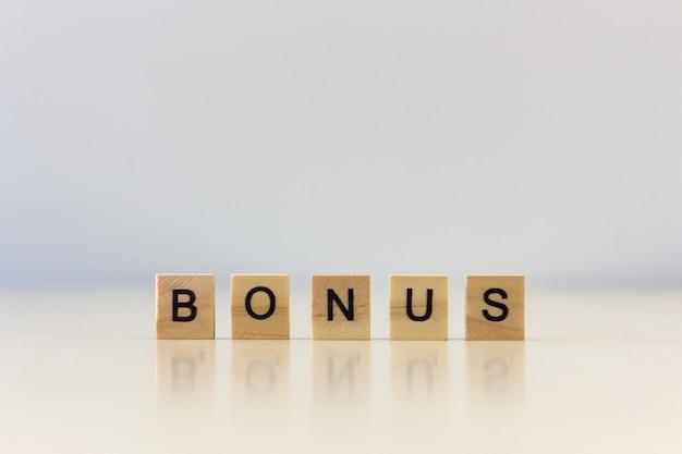 Hölzerner würfel des bonus-wortes auf holztisch