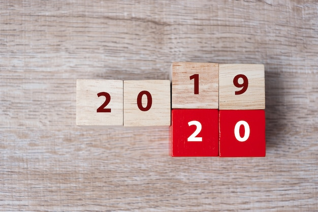 Hölzerner würfel mit schlag über block 2019 bis wort 2020 auf tabellenhintergrund