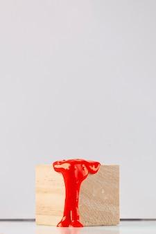 Hölzerner würfel mit tropfender orange farbe