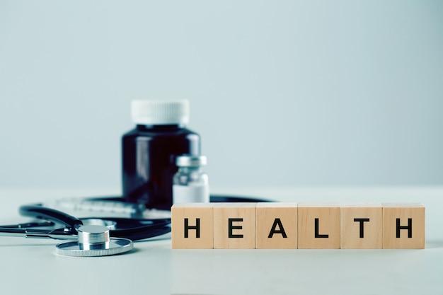 Hölzerner würfelblock mit wort healh und medizinischen geräten auf dem tisch. versicherungs- und gesundheitskonzept