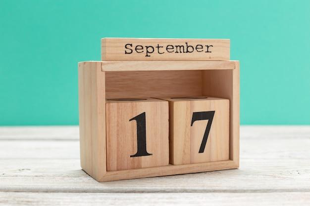 Hölzerner würfelformkalender für den 17. september auf hölzerner tischplatte