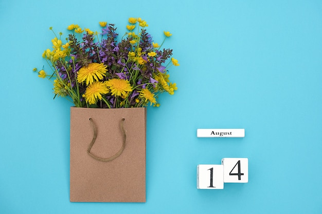 Hölzerner würfelkalender am 14. august und bunte rustikale blumen des feldes im handwerkspaket auf bluefor text und design
