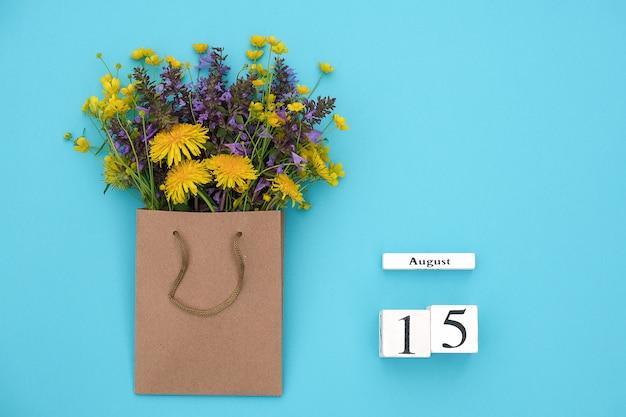 Hölzerner würfelkalender am 15. august und bunte rustikale blumen des feldes im handwerkspaket auf bluen