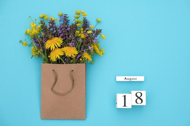 Hölzerner würfelkalender am 18. august und bunte rustikale blumen des feldes im handwerkspaket auf blauem hintergrund.