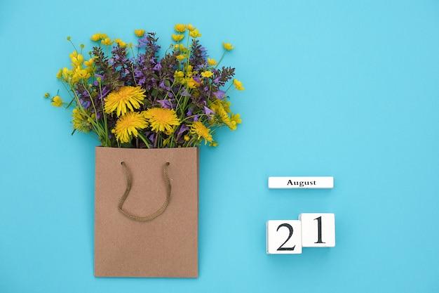 Hölzerner würfelkalender am 21. august und bunte rustikale blumen des feldes im handwerkspaket